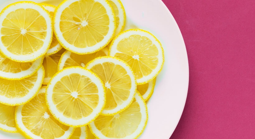 Aerial view of thinly sliced acidic lemons on a white plate on a pink counter