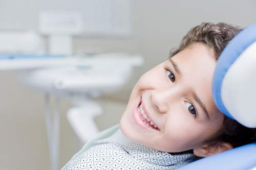 A young boy with brown hair in a polka-dot shirt, smiling as he reclines in the dental chair