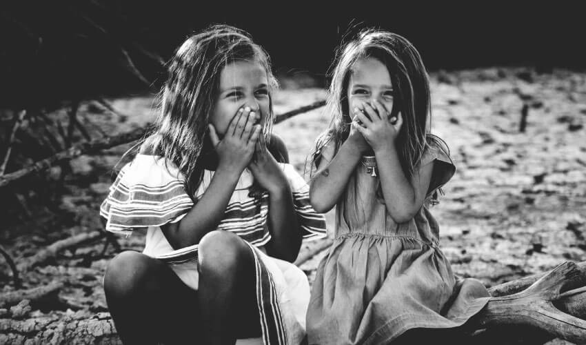 Black and white image of 2 young girls with loose baby teeth laughing and covering their mouths with their hands