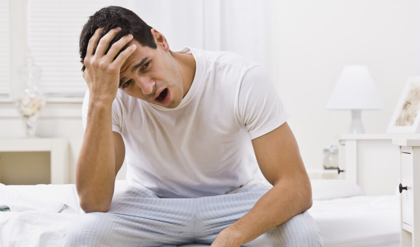 Brunette man in his pajamas yawns and has a morning headache and daytime sleepiness from sleep apnea