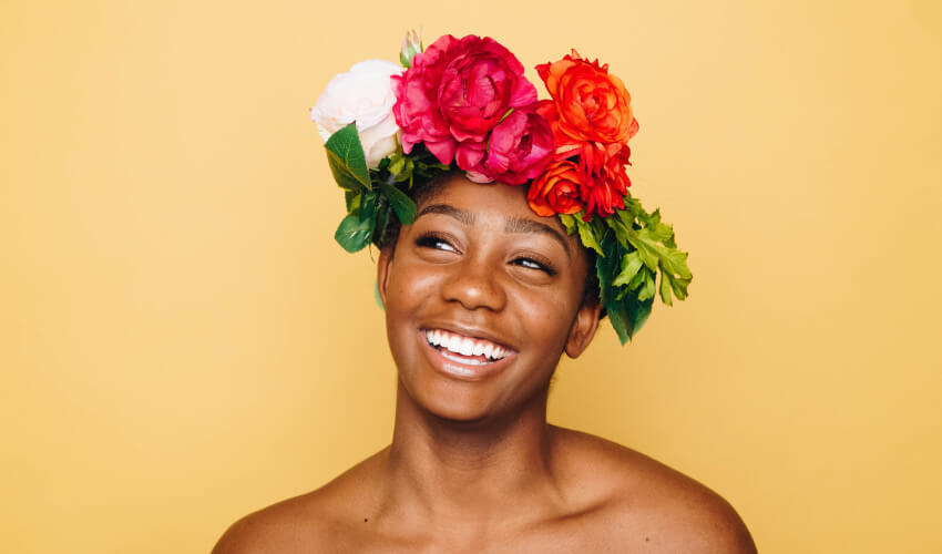 Woman smiles while wearing a floral crown of spring flowers
