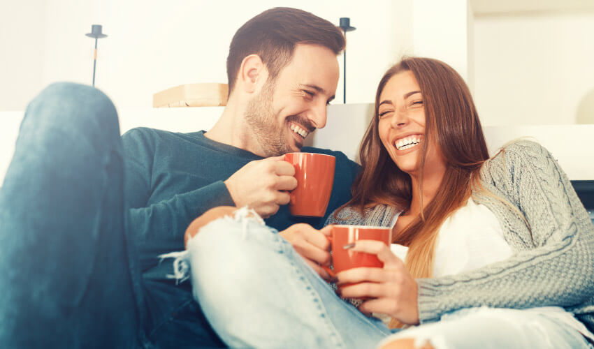 Man and woman smile with dental implants as they cuddle on a couch while holding orange mugs
