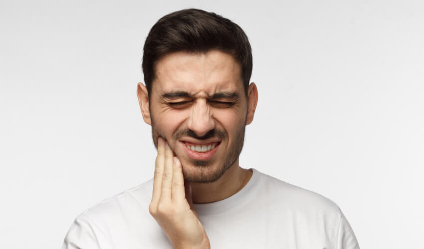 Brunette man in a white t-shirt cringes in pain and touches his cheek due to a toothache dental emergency