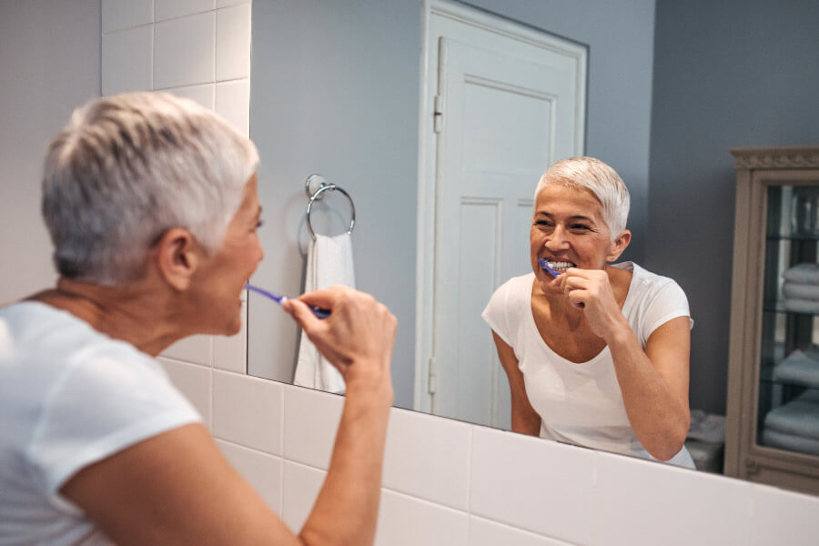 Lady with short gray hair brushes her teeth while looking in the bathroom mirror.