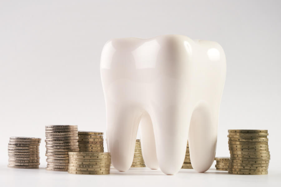 A large model of a tooth sitting among stacks of coins.