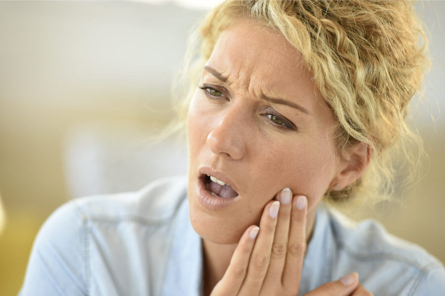 Blonde woman with her hand on her cheek indicating tooth pain.